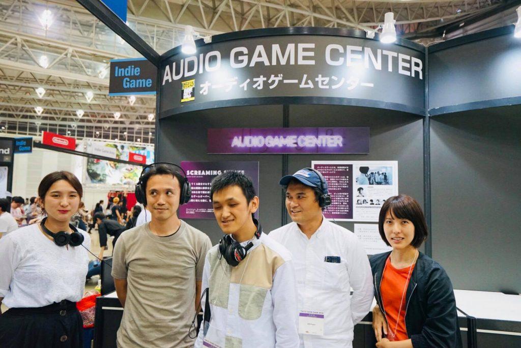 東京ゲームショウ2018にて。「オーディオゲームセンター」と書かれた出展ブースの前で記念撮影。