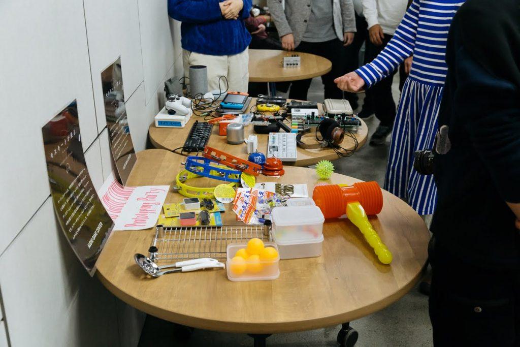 ハッカソンの材料として用意した音の鳴るおもちゃや日用品、家電などが机に置かれている。