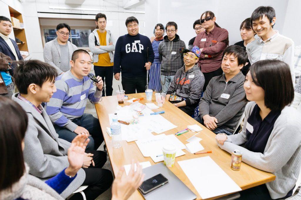 テーブルを囲み、デモンストレーションを行うグループ。周りで他の来場者が聞いている。
