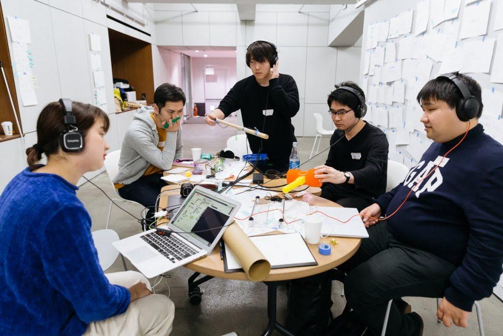 紙の筒などの素材を広げてディスカッションするグループ。