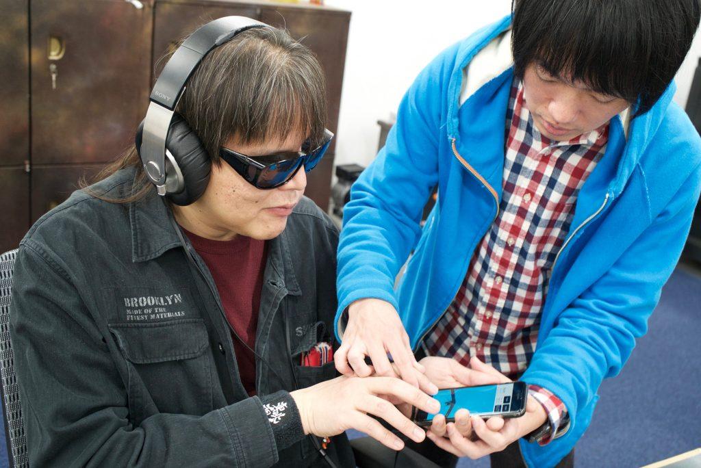 メンバーの加藤を岡田がサポートし、スマートフォンでバーチャル空間で音を配置し鳴らすアプリを試す。