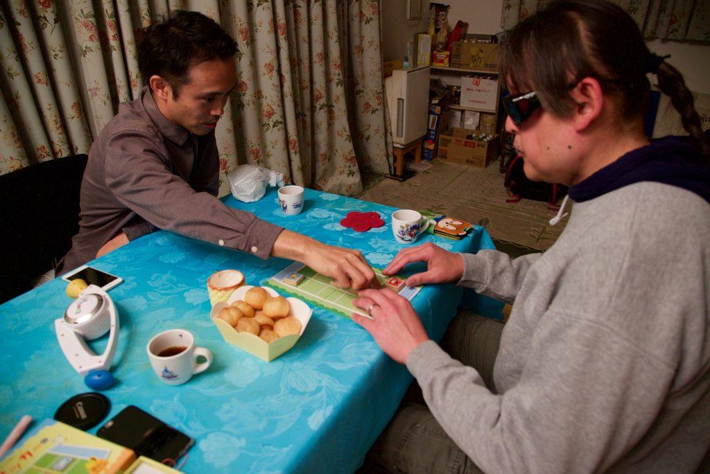 メンバーの加藤の家でテーブルを挟んでボードゲームで遊ぶ。