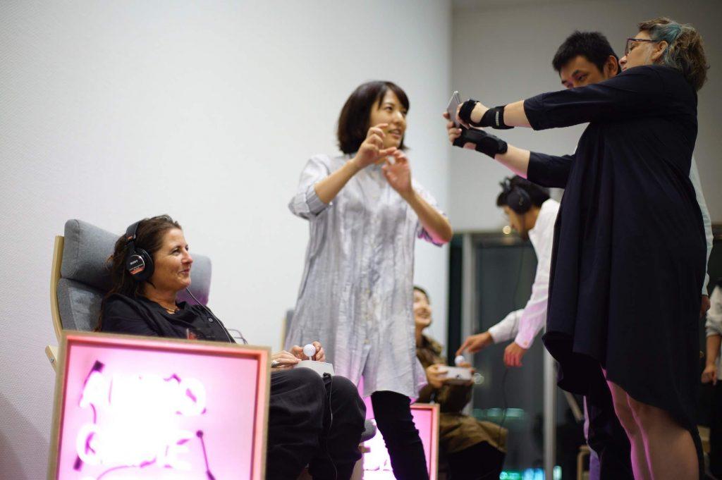 メンバーの田中と野澤が欧米人の来場者とやり取りする。