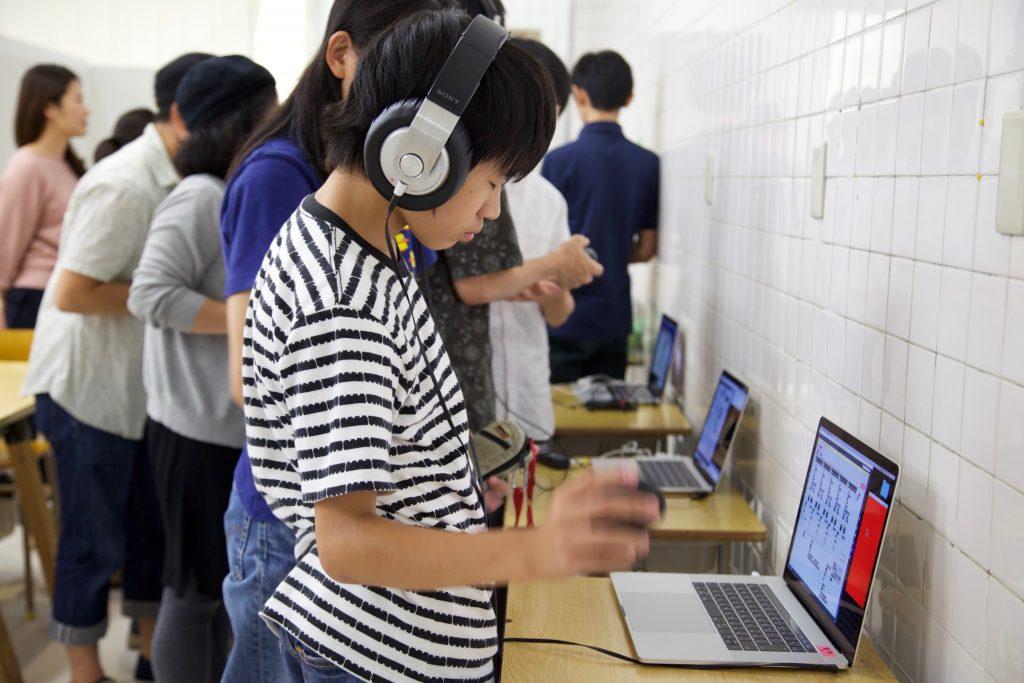 ヘッドフォンをつけ、目を閉じてプロトタイプをプレイする参加者。