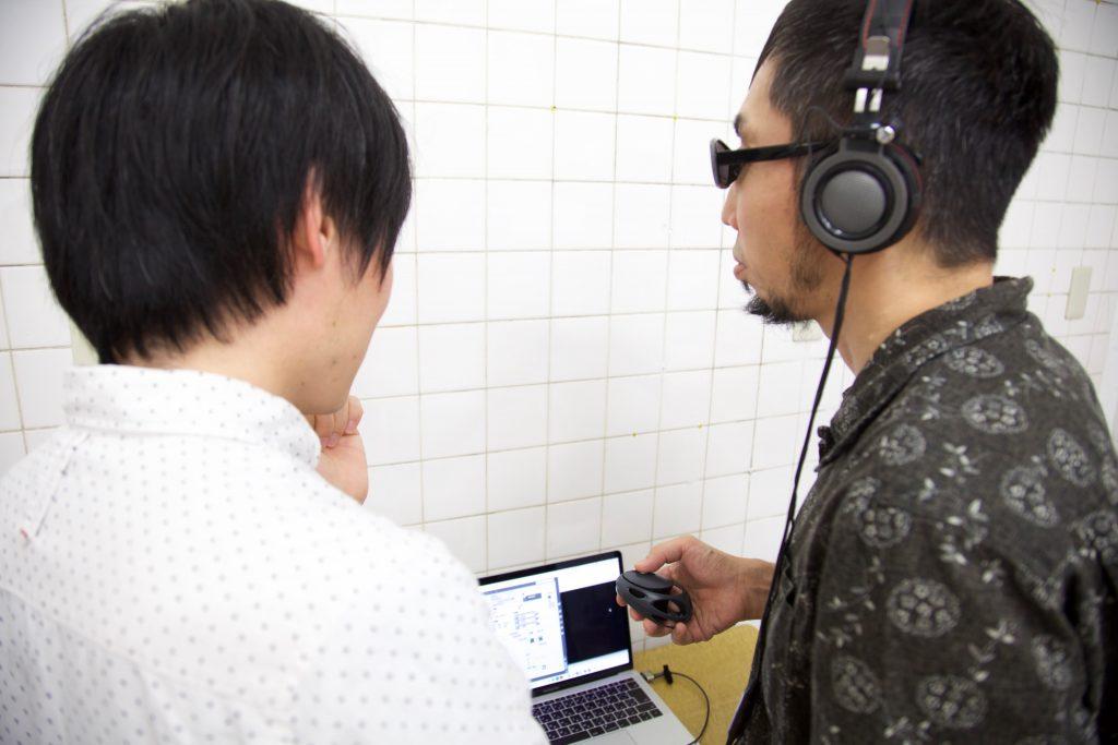 ヘッドフォンをつけた参加者にメンバーの岡田が説明を行う。