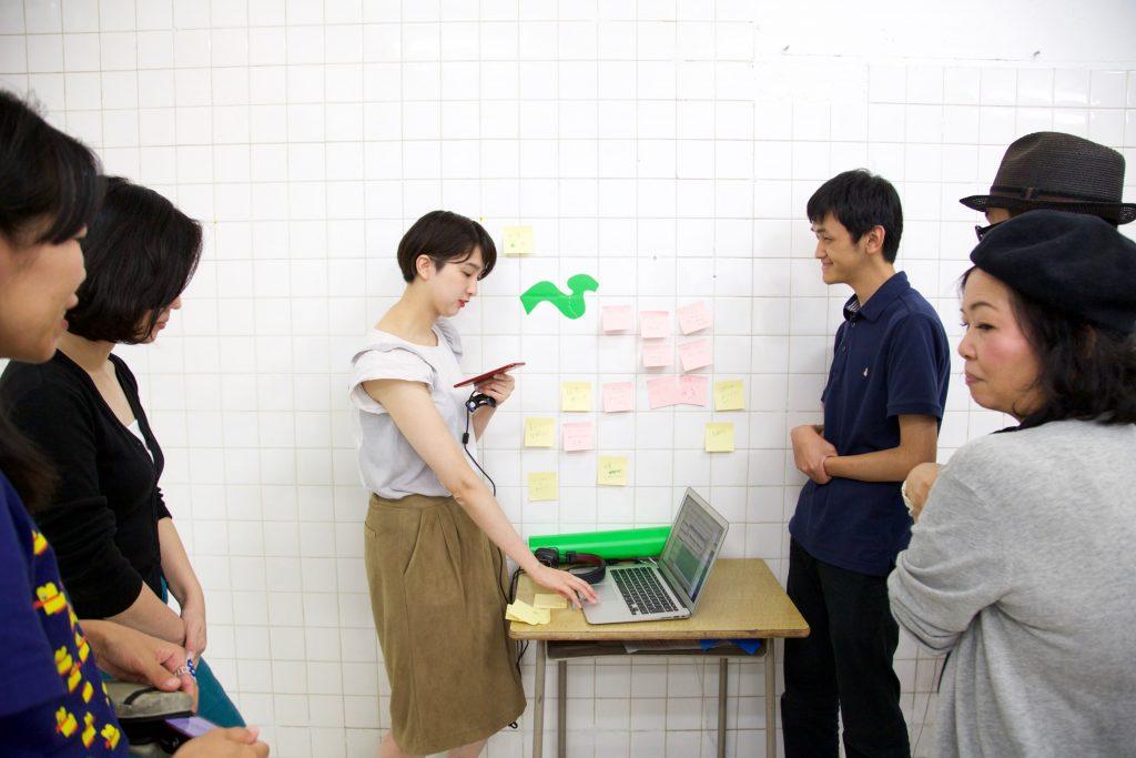 参加者にプロトタイプの説明を行う和田と野澤。壁には複数のポストイットが貼られている。