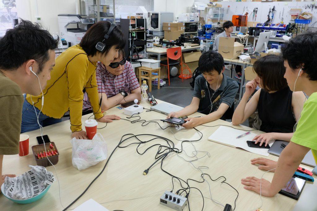 開発ミーティングの様子。野澤のゲームの音を他のメンバーが身を乗り出して聴く。